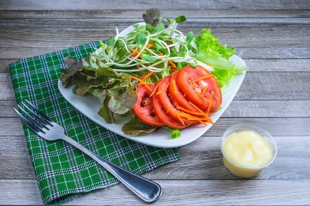 Frischer salat und salatdressing für gesundheit auf einem holztisch