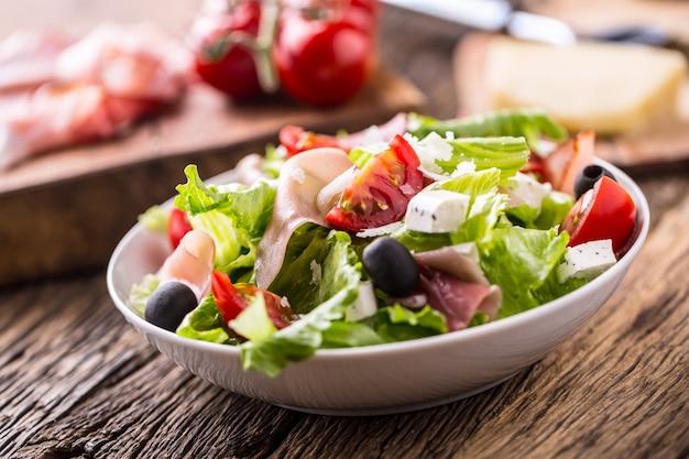 Frischer salatsalatgesunder mediterraner salat oliven tomaten parmesankäse und prosciutto
