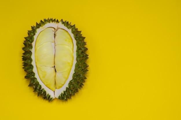 Frischer schnitt durian, der könig der frucht von thailand ist, lokalisierte auf gelbem hintergrund mit raum für text.