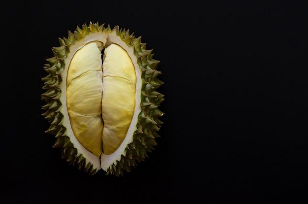 Frischer schnitt durian, der könig der frucht von thailand ist, lokalisierte auf schwarzem hintergrund mit raum für text.