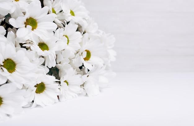 Frischer schöner blumenstrauß des weißen gänseblümchens auf weißem schreibtisch