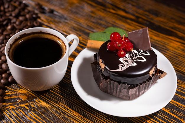 Frischer schwarzer kaffee in der tasse durch schokoladencupcake
