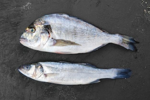 Frischer seebarsch und seebrassenfisch auf schwarzem stein