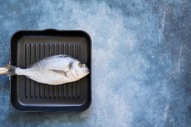 Frischer seebrassenfisch in der tropfenden pfanne auf blauem tisch. draufsicht, kopierraum.