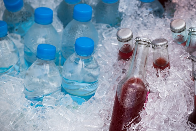 Frischer selbst gemachter erdbeersaft und trinkwasser in flaschen mit kaltem eis.