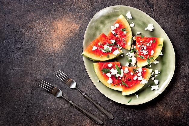 Frischer sommer grillte wassermelonensalat mit feta, minze, zwiebeln auf braunem hintergrund