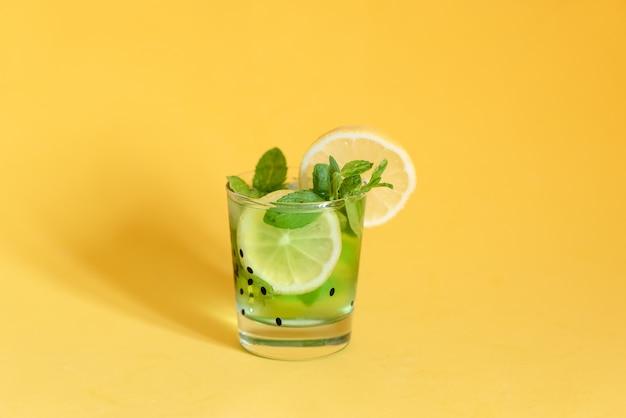 Frischer sommer trägt wasser oder limonade mit zitrone, orange und minze auf gelb früchte