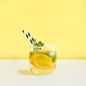 Frischer sommer trägt wasser oder limonade mit zitrone, orange und minze auf gelbem hintergrund früchte. nahansicht.