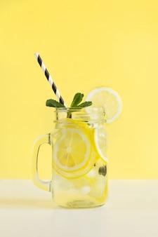 Frischer sommer trägt wasser oder limonade mit zitrone und minze auf gelbem hintergrund früchte. nahansicht.