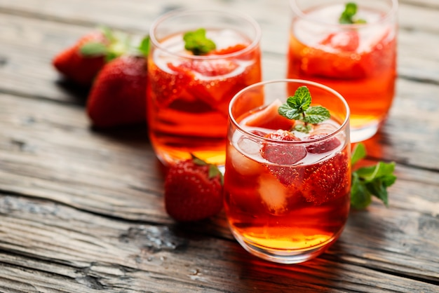 Frischer sommercocktail mit eis, erdbeere und minze