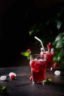 Frischer sommerlicher kalter cocktail mit himbeere, minze und eis. balkenkonzept und selektives fokusbild