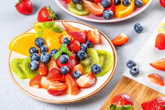 Frischer sommersalat aus verschiedenen früchten und beeren. kiwi, orange, erdbeere und blaubeere auf einem mit minze dekorierten teller auf einem tisch hautnah.