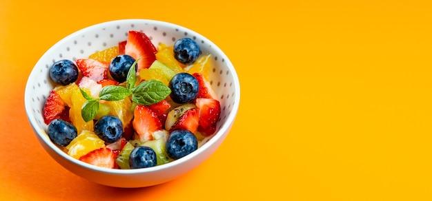 Frischer sommersalat aus verschiedenen früchten und beeren. kiwi, orange, erdbeere und blaubeere auf einem mit minze dekorierten teller plate