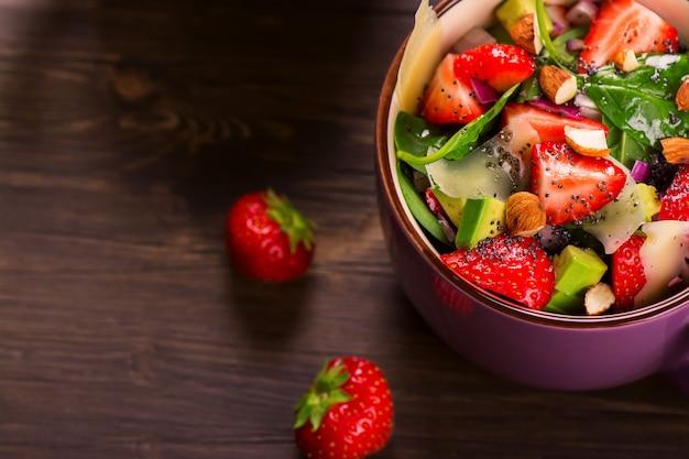 Frischer sommersalat mit erdbeere, avocado und spinat auf rustikalem hölzernem hintergrund