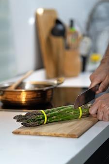 Frischer spargel auf küche mit mannhand, koch, der spargel schneidet.