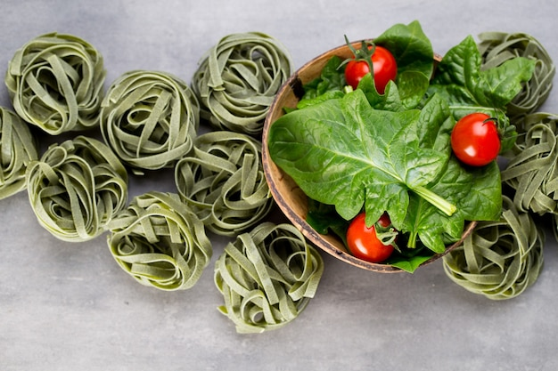 Frischer spinat mit grünen nudeln auf einem grau