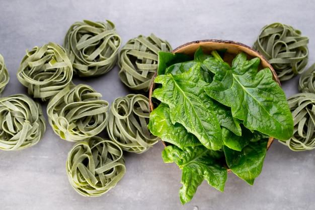 Frischer spinat mit grünen nudeln auf grauem hintergrund.