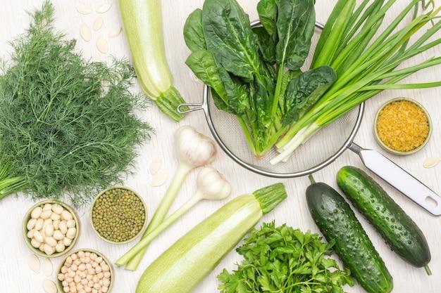 Frischer spinat und frühlingszwiebelblätter im sieb. kichererbsen, mungobohnen und nüsse in schalen. knoblauch, gurken und zucchini auf dem tisch. weißer hintergrund. flach liegen.