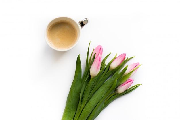 Frischer strauß von fünf tulpen lokalisiert auf weißem hintergrund mit einer tasse kaffee. frühlingsblumen.