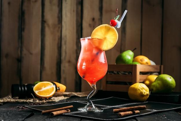 Frischer süßer cocktail-sex am strand in einem glas mit strohhalm auf dem dunklen hölzernen hintergrund, seitenansicht, horizontal
