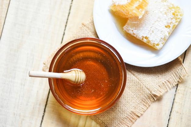 Frischer süßer honig im glas mit hölzernem schöpflöffel und bienenwabe auf platte auf hölzerner tabelle