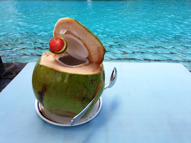 Frischer süßer kokosnusssaft auf dem tisch und poolhintergrund