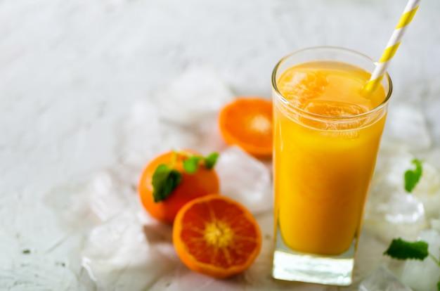 Frischer tangerinesaft im glas. orange früchte mit eis, minze. kaltes getränk für heiße sommertage. exemplar