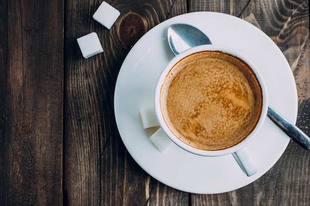 Frischer tasse kaffee und zucker auf altem rustikalem tabellenhintergrund. morgen-konzept