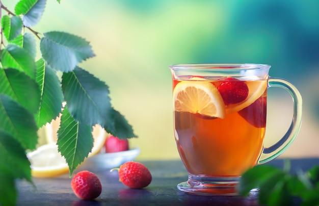 Frischer tee mit zitrone und erdbeeren in einer großen glastasse