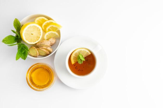 Frischer tee mit zitrone und honig auf einem weißen hintergrund