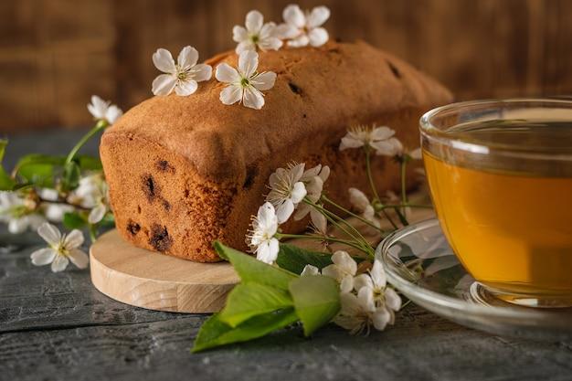 Frischer tee und ein muffin mit rosinen auf dem rustikalen tisch. hausgemachte süßigkeiten nach alten rezepten.