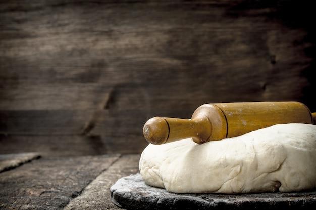 Frischer teig mit nudelholz. auf einem hölzernen hintergrund.