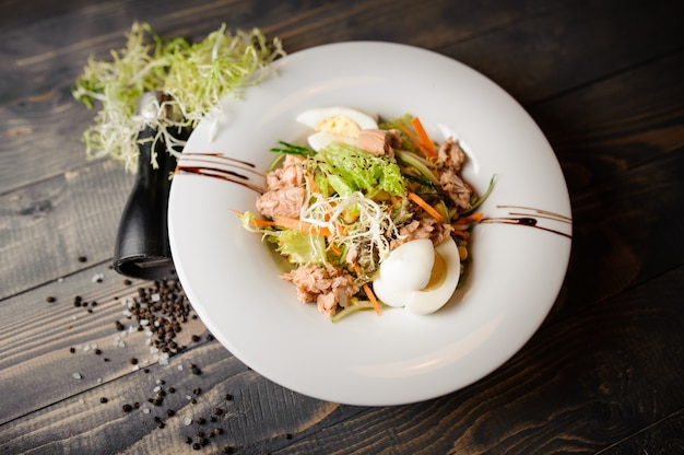 Frischer thunfischsalat mit eiern, tomaten, bohnen, oliven auf weißem teller.