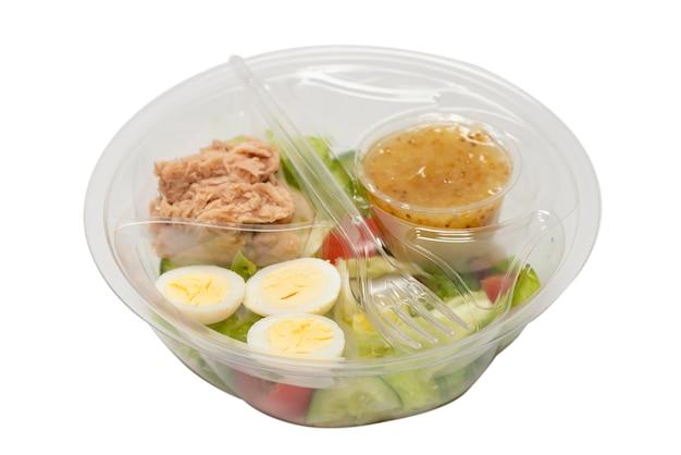 Frischer thunfischsalat mit salat, gurken, kirschen und eiern im plastikbehälter. ansicht von oben.