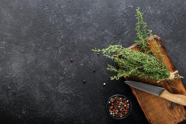Frischer thymian auf einem küchenbrett mit messer und gewürz auf schwarzem hintergrund.