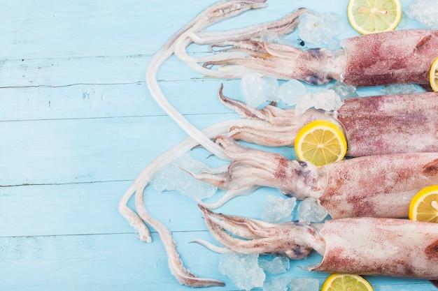 Frischer tintenfisch oder tintenfisch roh auf holzbrett mit zutaten