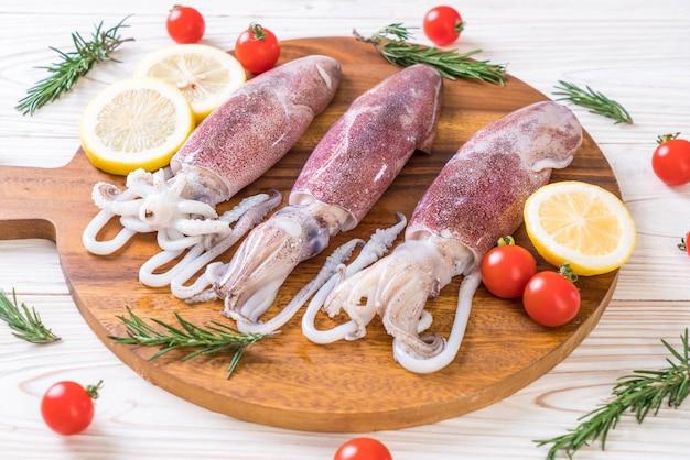 Frischer tintenfisch oder tintenfische roh auf holzbrett