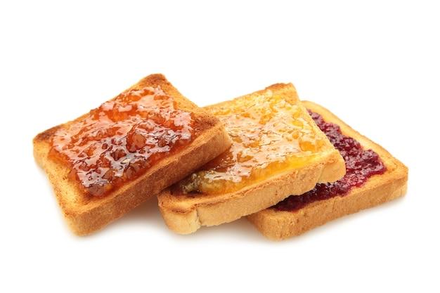 Frischer toast mit butter und verschiedenen marmeladen auf weißem hintergrund. ansicht von oben