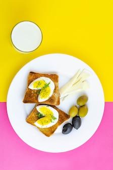 Frischer toast mit eiern, oliven und sojakäse zum frühstück und ein glas milch mit rosa und gelb.
