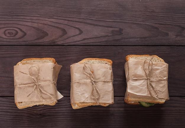 Frischer toast mit lachs, frischkäse und gemüse liegt auf einem stapel, eingewickelt in bastelpapier.