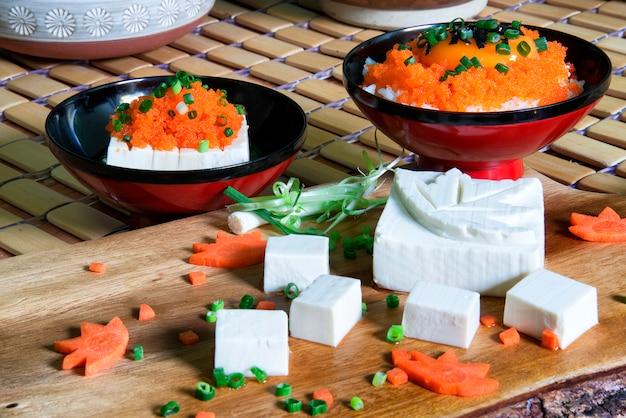 Frischer tofu im japanischen stil, in geschnitzter form mit einem mit frühlingszwiebeln verzierten mepelblatt