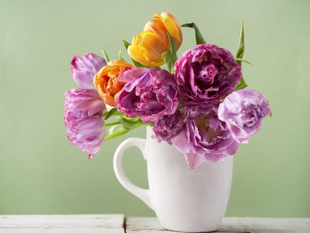 Frischer tulpenblumenstrauß in der tasse
