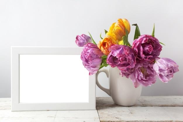 Frischer tulpenblumenstrauß und leerer fotorahmen
