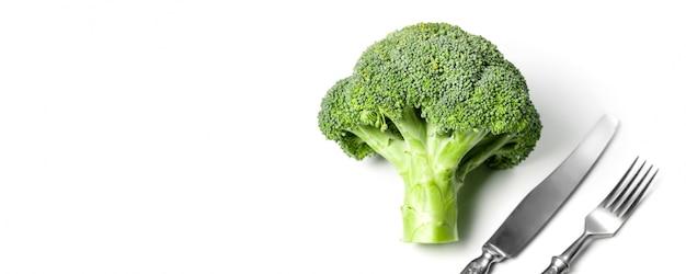 Frischer umweltfreundlicher brokkoli gegen weiß mit gabel und messer