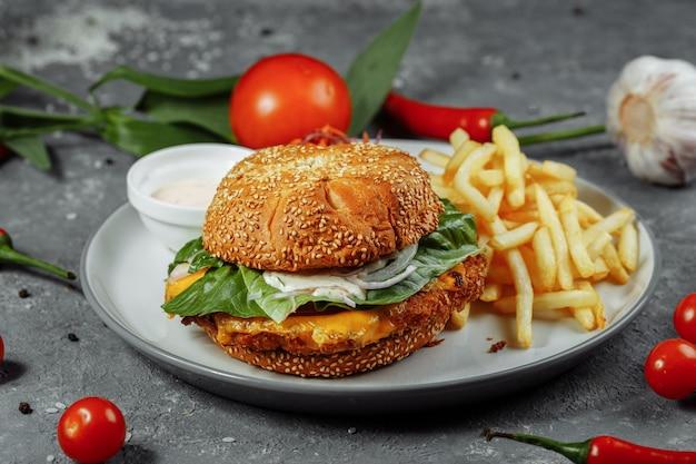Frischer und gebratener fischburger mit gemüse.