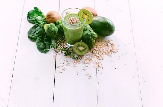 Frischer und geschmackvoller grüner smoothie mit bestandteilen auf holzoberfläche