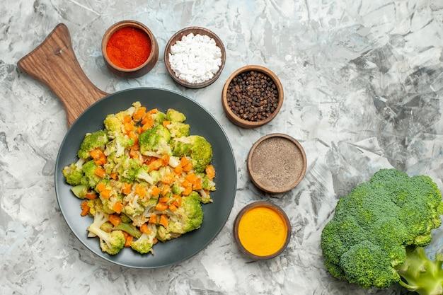 Frischer und gesunder gemüsesalat auf hölzernem schneidebrett und gewürzen auf weißem tisch