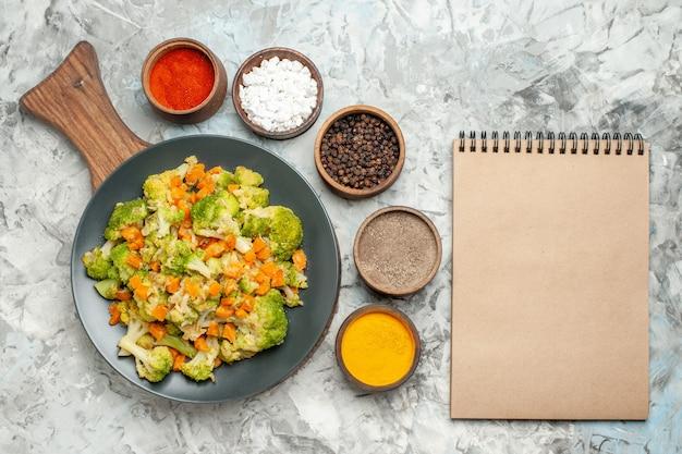 Frischer und gesunder gemüsesalat auf hölzernem schneidebrett und notizbuch auf weißem tisch
