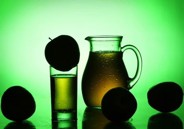 Frischer und kalter apfelsaft im grünen scheinwerferlicht