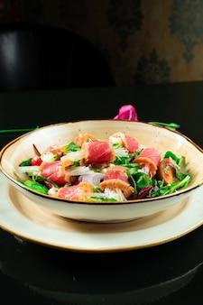 Frischer und köstlicher tataki-salat mit thunfisch, salat, roten zwiebeln, kirschtomaten und daikon-rettich. leckerer meeresfrüchtesalat der japanischen küche in der gelben schüssel auf dunklem hintergrund.